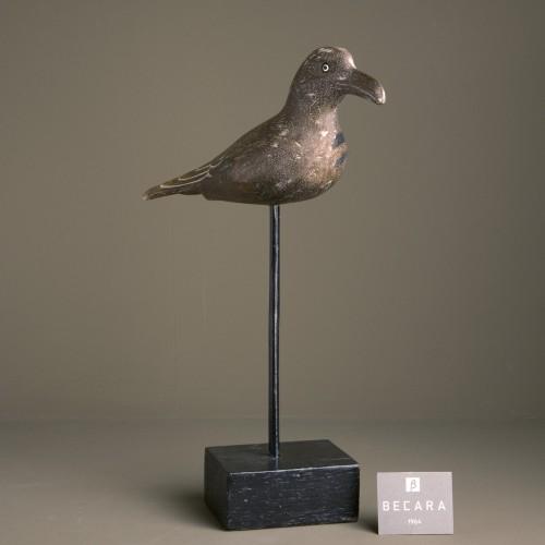Pájaro marrón en peana alta