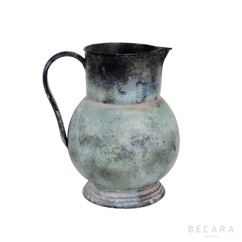 Green metal jug with tassel